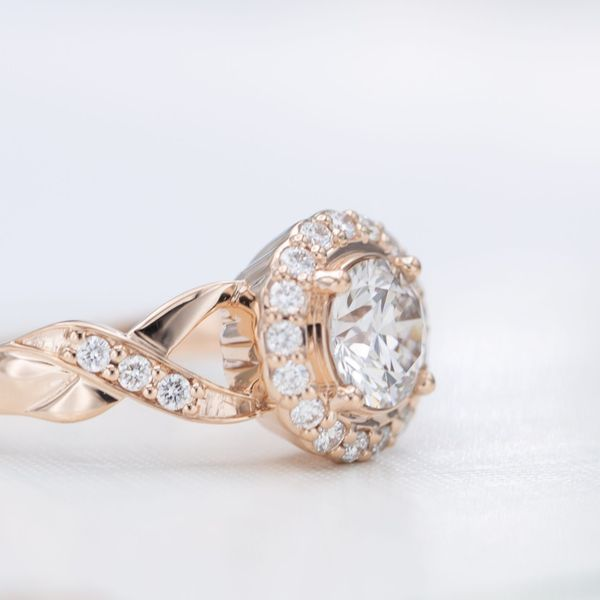 This ring's halo slopes away from the center stone for a more understated setting.