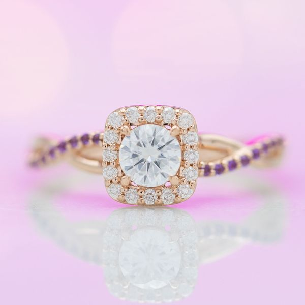 A soft square halo frames this engagement ring's round center stone.