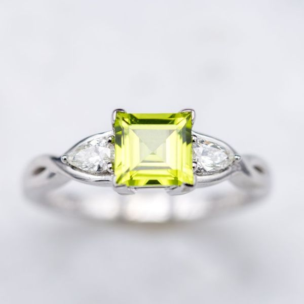 A modern ring with the crisp apple green of peridot flanked by a pair of pear cut diamonds.