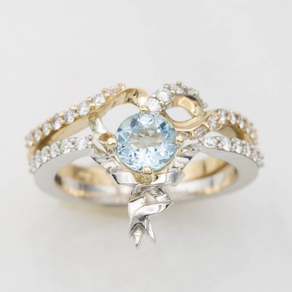 Designed to look like ribbons twisting in white and yellow gold, this engagement ring and wedding band sit together and form a heart shape around the center aquamarine.