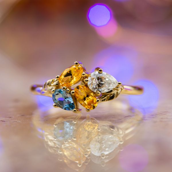 A modern, asymmetric cluster combines aquamarine, diamond and yellow topaz in a beautiful setting.