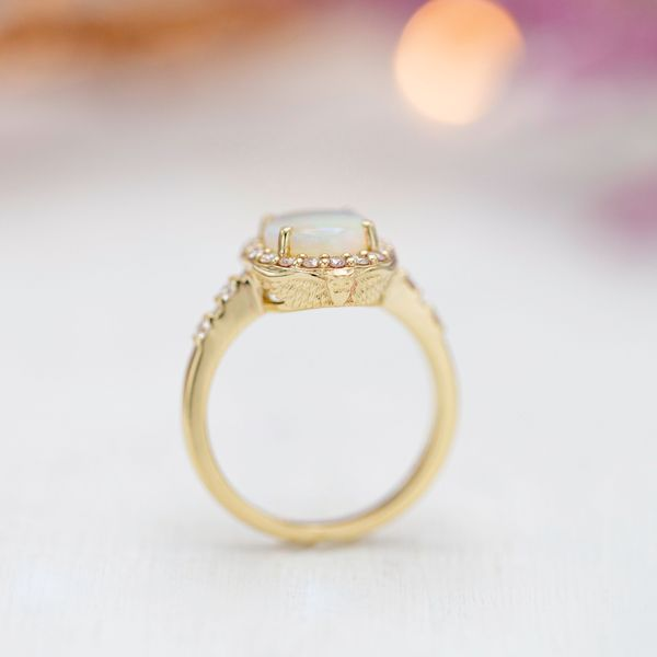 The opal ring's basket is framed by an owl with its wings spread majestically.