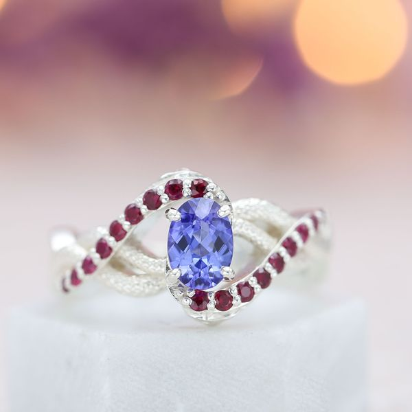 An open spiral of textured metal and accent gems creates a bold setting for the bright, lavender tone of this tanzanite.