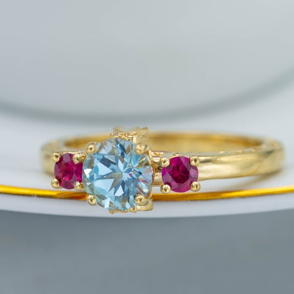For a woman who loves colored gems and competes as a ballroom dancer, we designed this ring with sky blue topaz and ruby, featuring silhouettes of a dancing couple on the side of the setting.