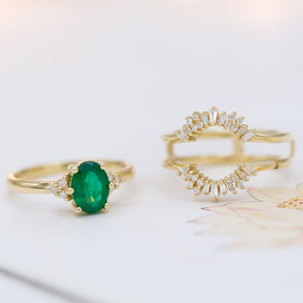 A minimal emerald engagement ring is matched by a two-band surrounding wedding ring, which frames the center stone with a ballerina halo.