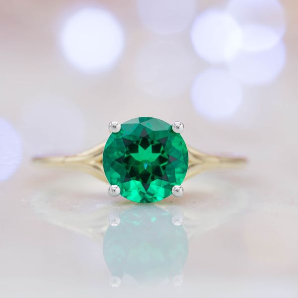 A delicate yellow gold band pairs perfectly with the clear green of this lab-created round brilliant emerald. A sleek, contemporary ring with just a slight curve as the shank splits open around the center setting.
