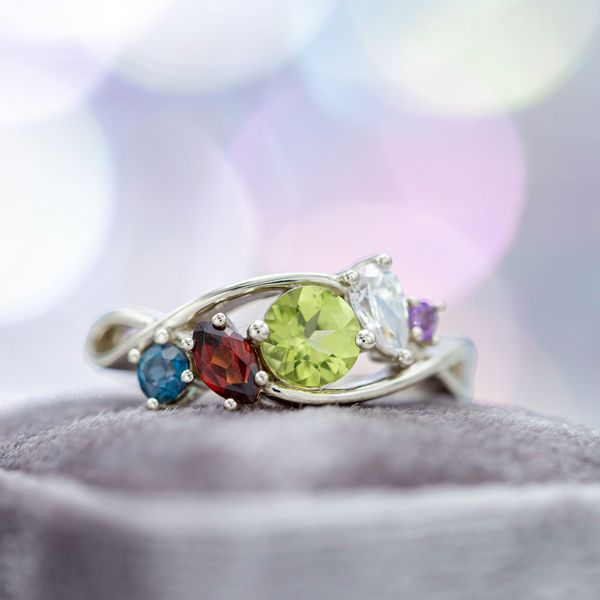 Whimsical cluster engagement ring with peridot, garnet, topaz and amethyst.