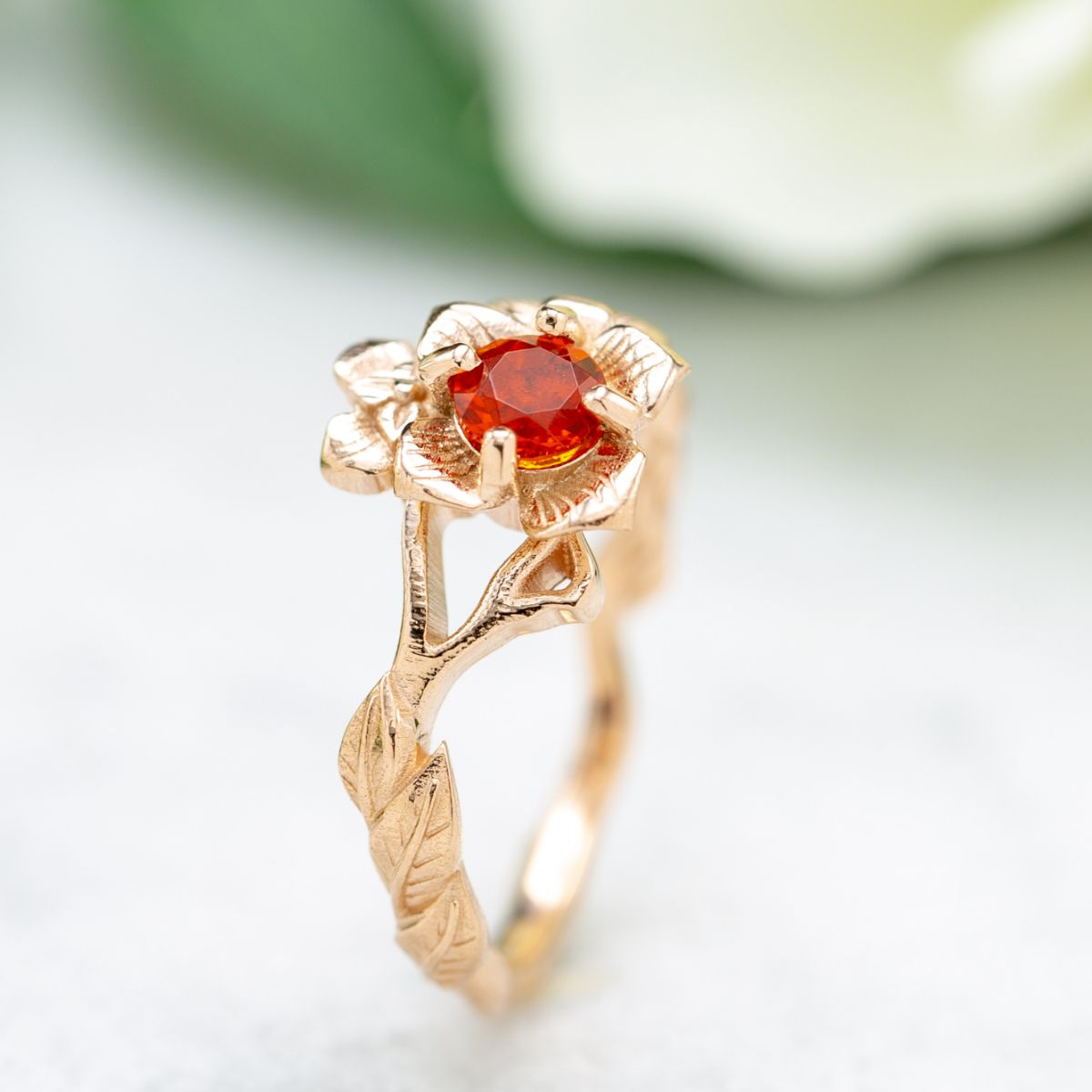 Inspired by the persimmon, the blossom in this rose gold ring features a cherry fire