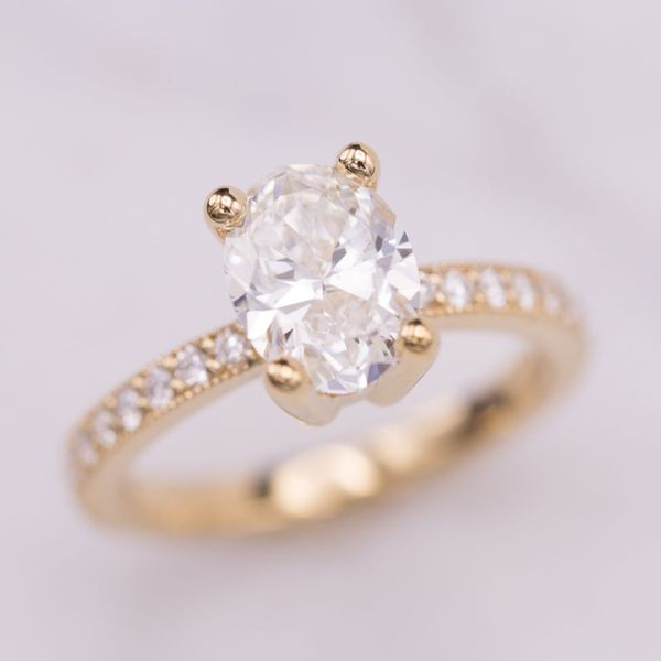 An instant classic with a 1.7ct oval diamond in 14k yellow gold with channel set diamonds and milgrain edges.