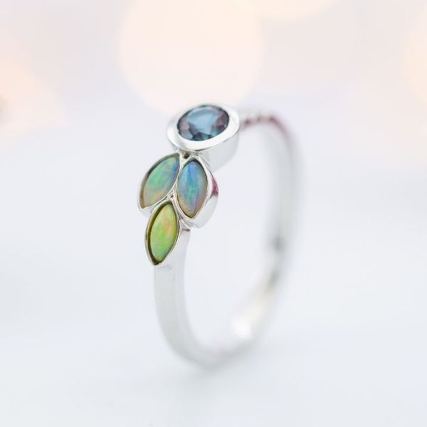 Marquise cut white opals create a pretty asymmetrical accent cluster in this modern alexandrite ring.
