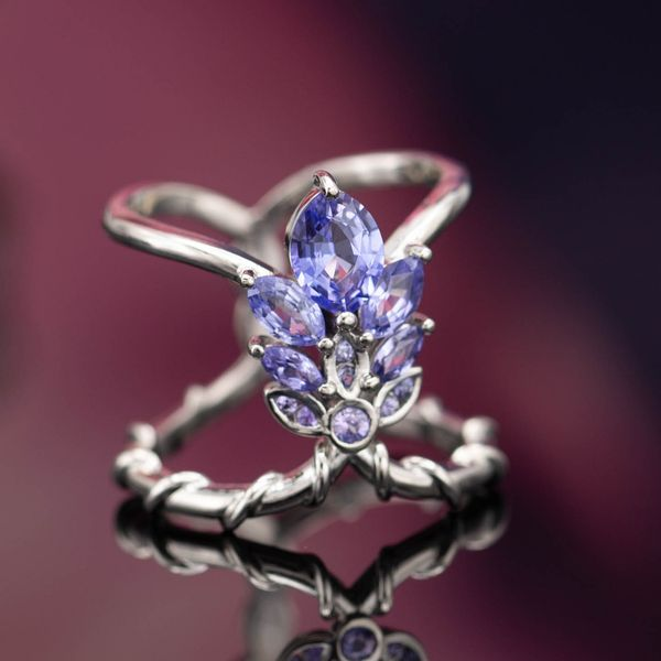 Custom cut purple sapphires create the look of the lavender flower, stretching along the finger between two vining bands.