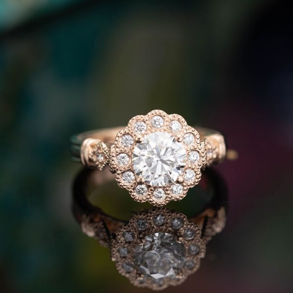 Using milgrain-lined bezel settings for this ring's halo creates a very floral setting and the styling of an antique ring.