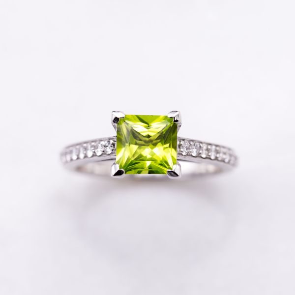 A bright, princess cut peridot is set with v-prongs in a sleek white gold band with channel set diamonds.