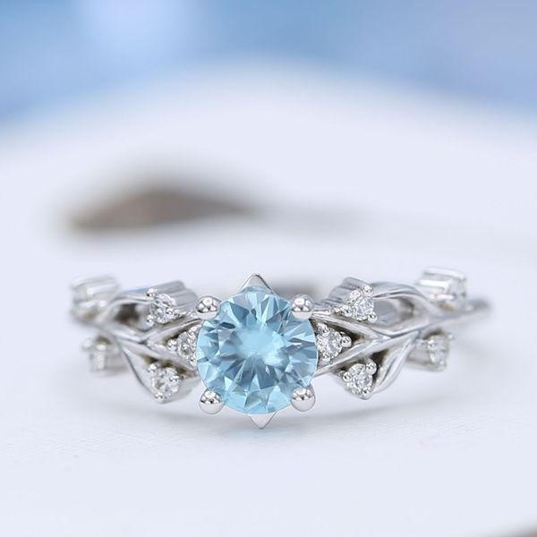 Blue zircon engagement ring with antler-inspired branching band and diamond accents.