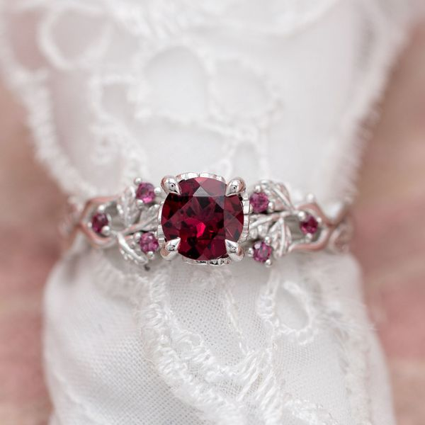 The pinkish-red of rhodolite garnet is the start of this nature-inspired engagement ring.