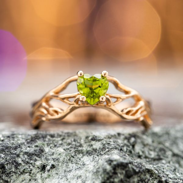 This nature-inspired ring creates a delicate mesh of rose gold roots to hold the heart cut peridot center stone.
