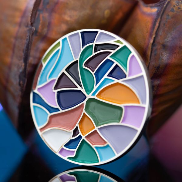 A beautiful enamel brooch whose colors and design are inspired by a stained glass window.