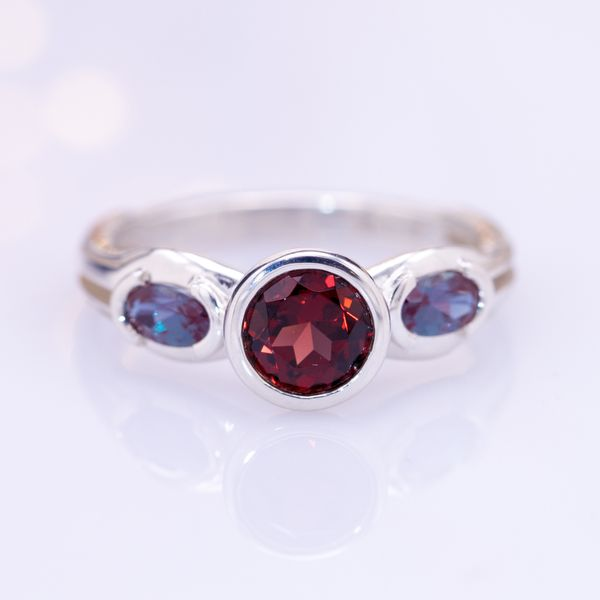 A modern bezel setting for the round garnet center stone, flanked by two oval lab-created alexandrites.