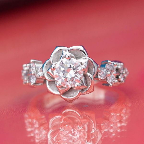 White gold flower engagement ring with softly tapered petals and diamonds.