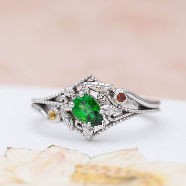 Turtle engagement ring with a pear cut tsavorite garnet as the center stone and turtle shell.