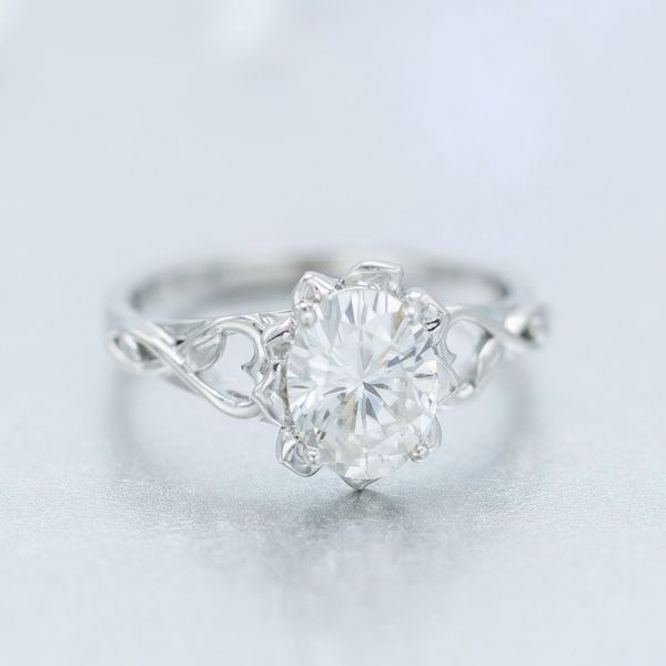 Oval moissanite engagement ring with a flower blossom setting and infinity-heart details on the band.