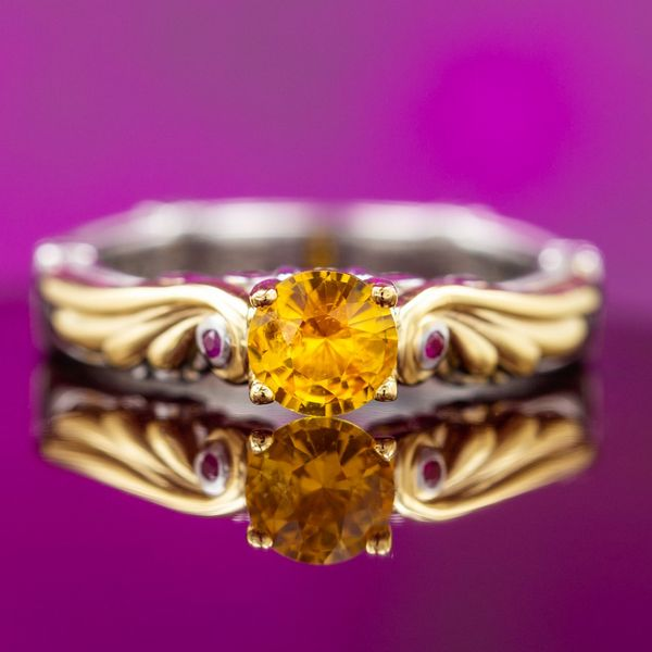 A warm orange-hued yellow sapphire is framed by gold wings in this ring.