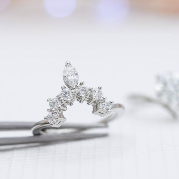 The wedding band is all sparkle, bringing a ton of glamor to balance the minimal engagement ring.