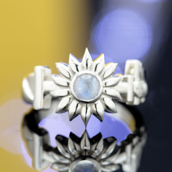 A unique sunflower design with a moonstone at its center and angular elements along the band.