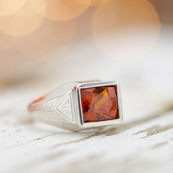 A bold, Art Deco-inspired ring with a fiery orange hessonite garnet center stone.