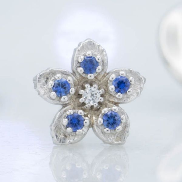 This pretty little flower brooch sets blue and white sapphires in the white gold petals.