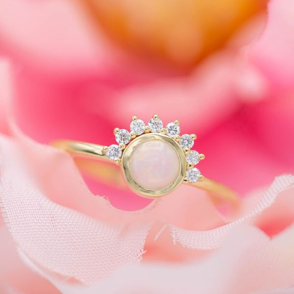 A delicate, modern opal ring with an asymmetrical sunburst half-halo.