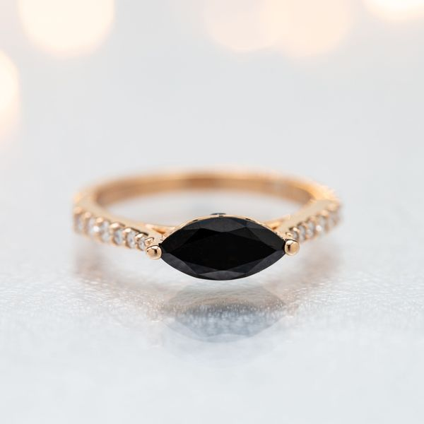 An east-west setting for this onyx center stone stretches the marquise gem across the finger for a distinctive, modern look.