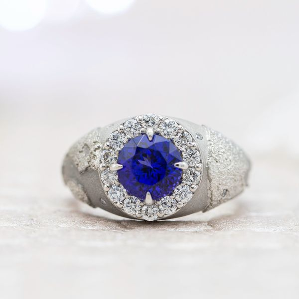 This bold, unique engagement ring surrounds the tanzanite center stone with a globe engraving, reflecting the couple's love of travel.