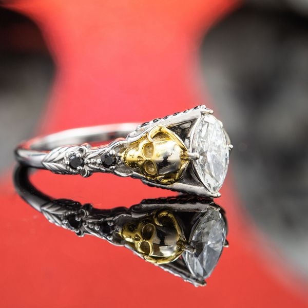 A pretty marquise cut center diamond flanked by skulls with black spinel accents.