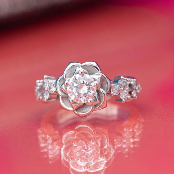 The softly curved petals of this platinum rose ring surround an 0.61ct round diamond.