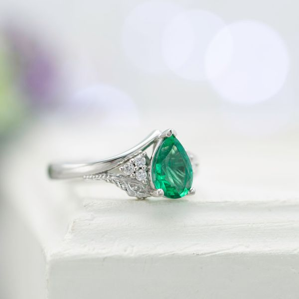 Pear emerald engagement ring with a peacock feather in the split-style shank framing the center stone.