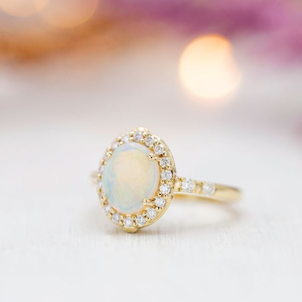The head-on view of this engagement ring shows the classic warmth of gold, shimmering white opal, and a sparkling diamond halo.