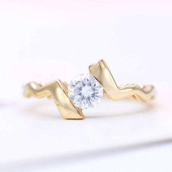 This uniquely shaped bypass engagement ring uses a tension-style setting to simulate the open, modern look but with a secure railing hidden under the center stone.