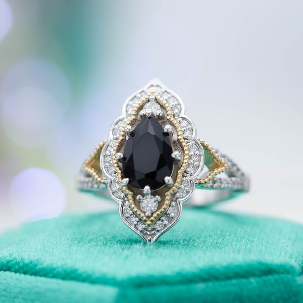 An elegant and bold vintage-inspired engagement ring surrounds a pear black diamond with a mixed yellow and white gold halo.