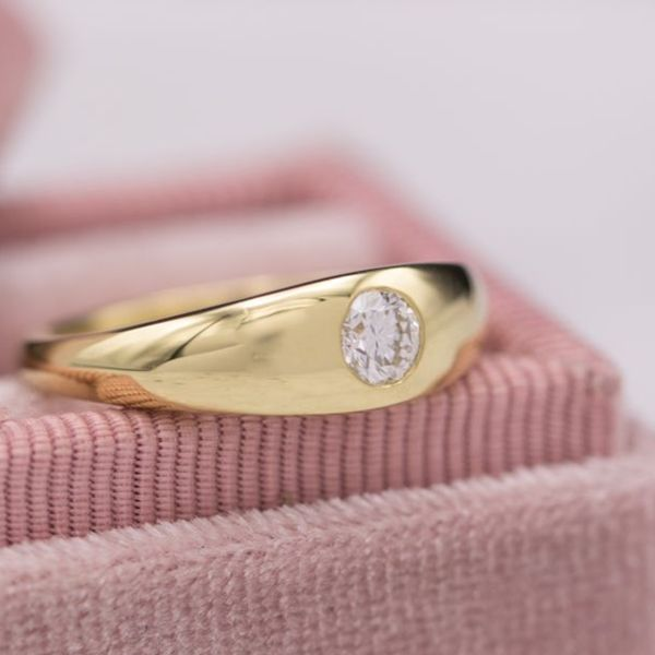 This diamond is flush set into the curvy gold shank of the ring.
