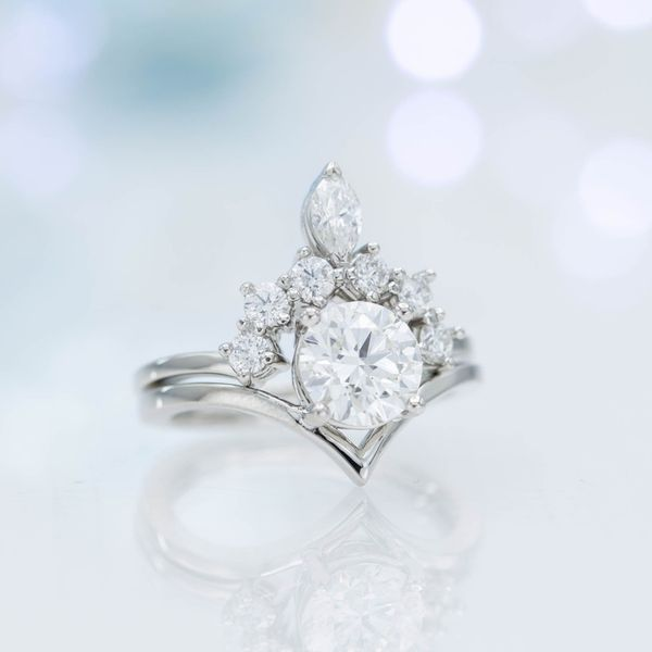 A perfect modern engagement ring gains classic, royal inspiration from the tiara-styled wedding band curving over it.