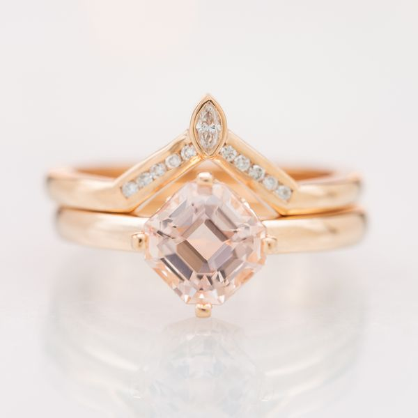 This bridal set pairs a kite set custom cut asscher morganite with a modern take on a tiara-inspired matching wedding band