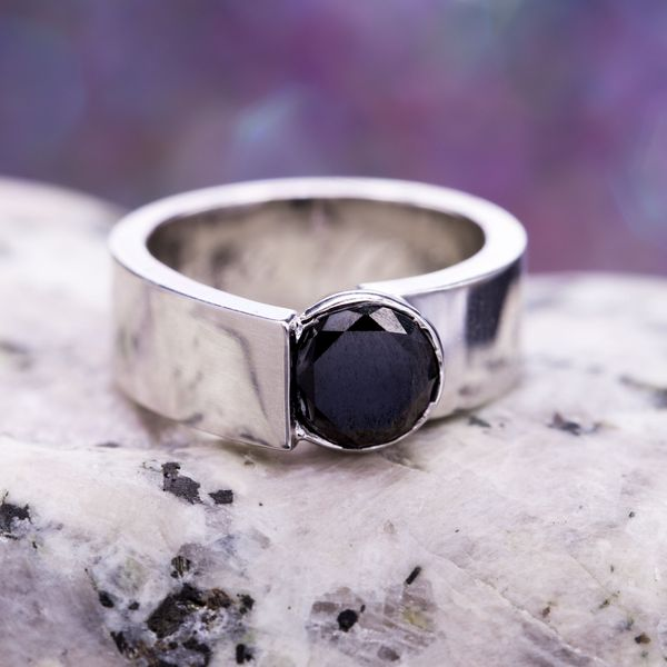 A bold, modern design with an asymmetric setting for a round cut black diamond