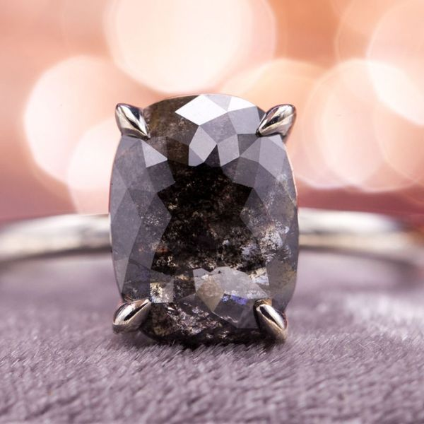 This engagement ring sets a very dark salt and pepper diamond, nearly black but still permitting hints of light to drift through the beautiful black inclusions that give the diamond its color.