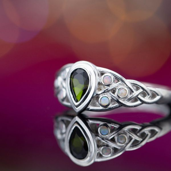 A Celtic ring with a deep green tourmaline (pear cut) surrounded by white opal accents.