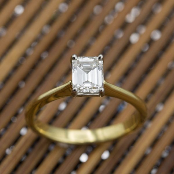 The perfect, elegant solitaire, with subtle taper and slope to the gold band to frame the emerald cut diamond.
