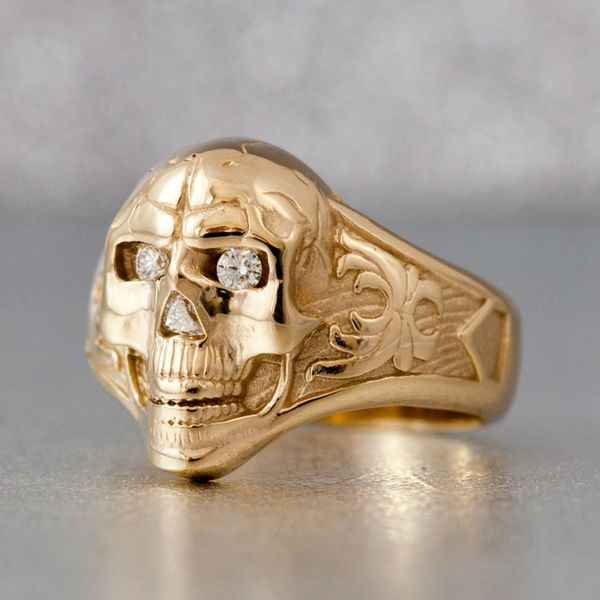A bold statement in yellow gold with triangle and round cut diamonds accenting the face of the skull.