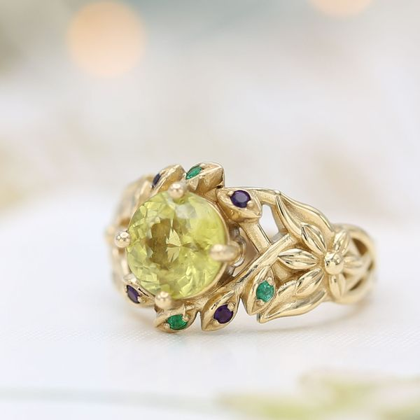 Chrysoberyl engagement ring with a floral theme and emerald and amethyst accents.