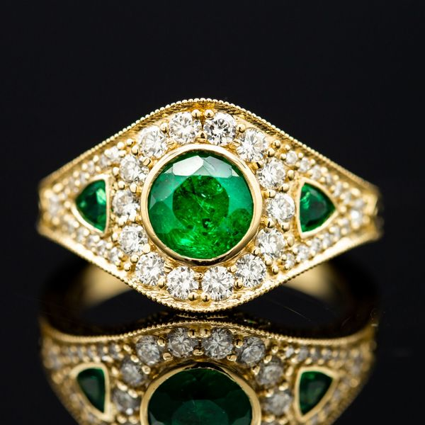 This gorgeous Art Deco-inspired ring sparkles with diamond accents, but the heart of the ring is a bright green emerald.