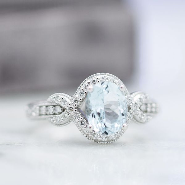 Vintage-inspired aquamarine engagement ring with a milgrain-edges halo braiding into a knot.
